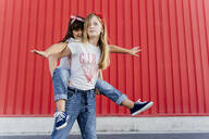 Girl carrying her sister on back, standing in front of a red wall - ERRF01618