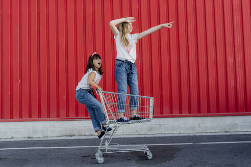 Sisters with shopping cart in front of red wall - ERRF01636