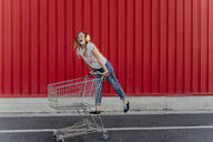 Girl with a shopping cart and ear defender in front of red wall - ERRF01654