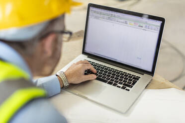 Architect using laptop at construction site - ZEF16153