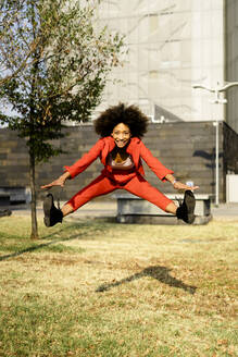 Portrait of happy young woman wearing fashionable red pantsuit jumping in the air - GIOF06863
