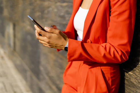 Woman wearing fashionable red pantsuit holding cell phone, partial view - GIOF06866