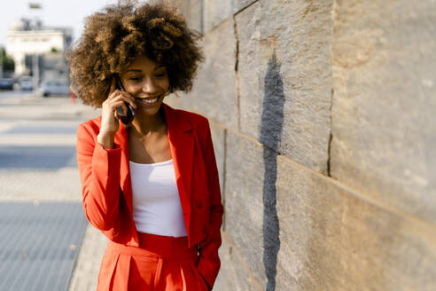 Portrait of smiling young woman on the phone wearing fashionable red pantsuit - GIOF06872
