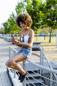 Portrait of tattooed young woman  taking selfie with smartphone in summer - GIOF06908