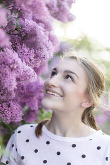 Deutschland, Jerichower Land, Gommern: Porträt einer jungen lächelnden Frau im Frühling vor einem Fliederbusch - JESF00242