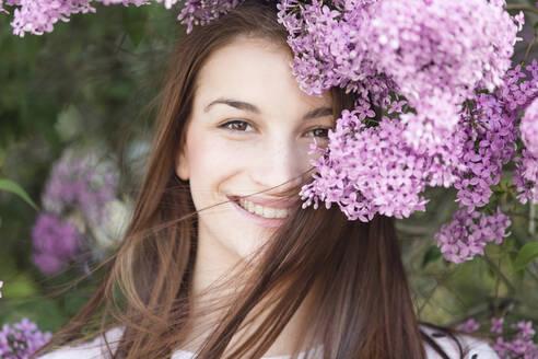 Deutschland, Jerichower Land, Gommern: Porträt einer jungen lächelnden Frau im Frühling vor einem Fliederbusch - JESF00245