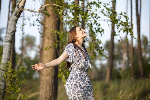 Deutschland, Jerichower Land, Gommern: Junge Frau im Kleid dreht sich vor Freude im Wald - JESF00248