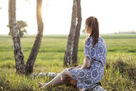 Young woman sitting on a tree trunk and enjoying sunset - JESF00251