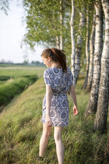Deutschland, Jerichower Land, Gommern: Junge Frau im Kleid läuft in einem Birkendwald entlang und sucht Entspannung - JESF00254