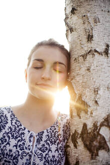 Young woman with closed eyes leaning on a tree trunk enjoying nature - JESF00260