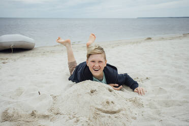 Portrait of happy blond boy with freckles wearing hooded jacket in front of Zeya River, Russia - VPIF01386