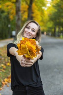Smiling woman presenting bunch of autumn leaves - JUNF01678