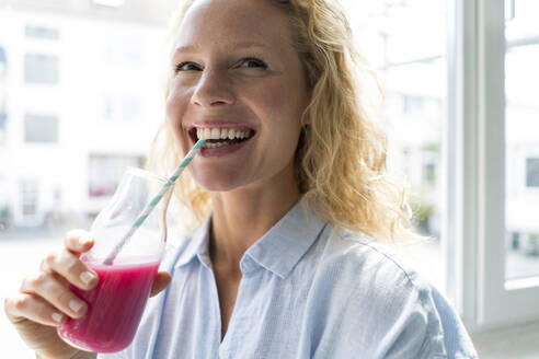 Smiling blond woman drinking a smoothie - JOSF03558
