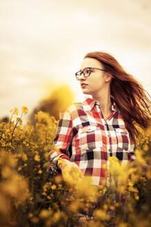 Feldweg, Deutschland, Baden-Württemberg, Nürtingen, junge Frau mit Brille, neugierig in einem blühenden Rapsfeld, Sehnsucht und Hoffnung - SEBF00112