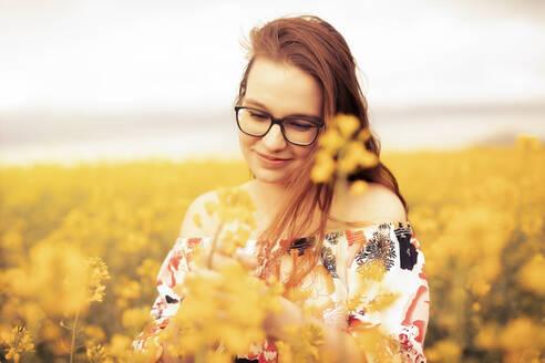 Feldweg, Deutschland, Baden-Württemberg, Nürtingen, junge Frau mit Brille lächelnd in einem blühenden Rapsfeld, Freude und Zufriedenheit - SEBF00115