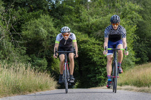 Triathletes riding bicycle on country road, Germany - STSF02138