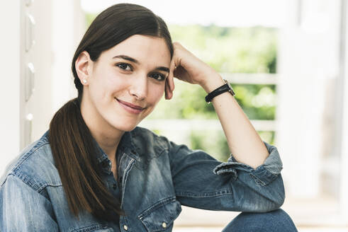 Portrait of smiling young woman wearing denim shirt at home - UUF18263