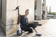 Smiling young woman with electric scooter, earphones and cell phone having a break in the city - UUF18296