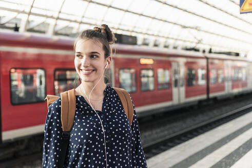 Portrait of smiling young woman at the train station - UUF18299