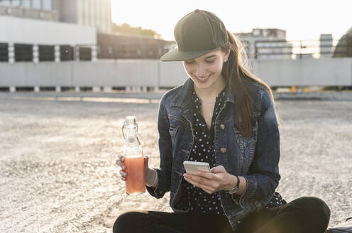 Smiling young woman with drink and cell phone sitting on parking deck at sunset - UUF18311