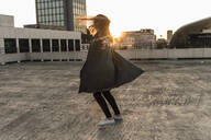 Cheerful young woman dancing on parking deck at sunset - UUF18347