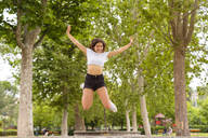 Young woman jumping in park - MGIF00639