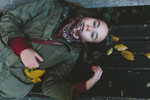 Deutschland, Köln, im Park, Portrait eines auf der Bank liegenden Mädchens - OGF00081