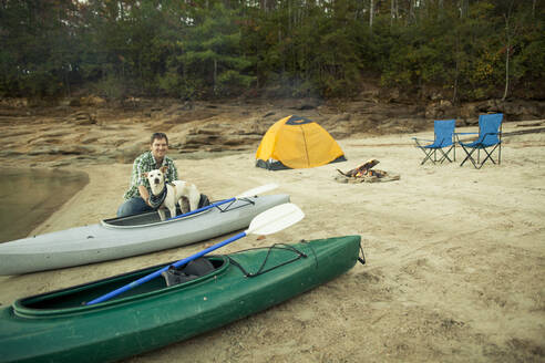 Man and dog with kayak at campsite - BLEF11957