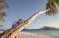 Asian woman on palm tree on beach - BLEF12011