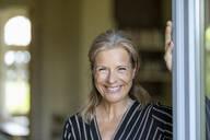 Portrait of smiling mature woman standing at opened terrace door - FMKF05743