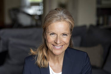 Portrait of smiling mature businesswoman at home - FMKF05749