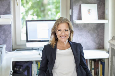 Portrait of smiling mature businesswoman at home office - FMKF05752