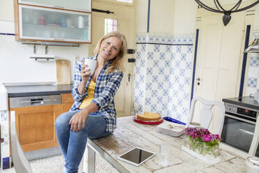 Portrait of smiling mature woman with coffee mug sitting on dining table in the kitchen - FMKF05755