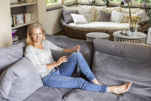 Portrait of blond mature woman relaxing on couch at home with digital tablet - FMKF05758