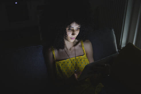 Young woman using her digital tablet in the night on the sofa - MRAF00421