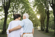 Back view of senior couple strolling in a park in the evening - AHSF00693