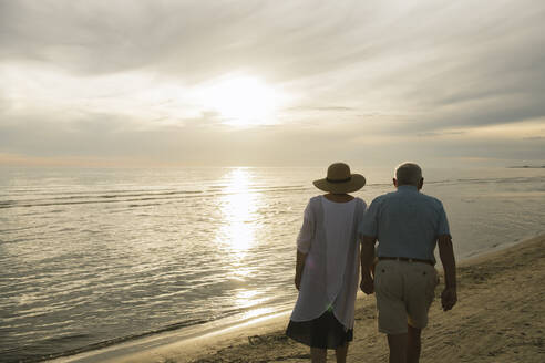 Back view of senior couple walking hand in hand on the beach at sunset, Liepaja, Latvia - AHSF00696