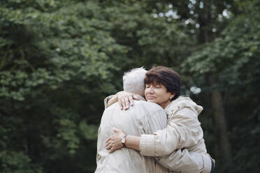 Portrait of senior woman hugging her husband in the woods - AHSF00699