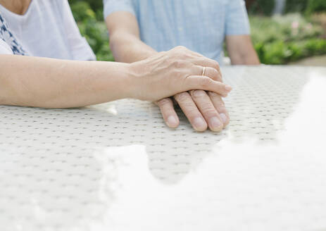 Senior couple sitting at garden table holding hands, close-up - AHSF00705