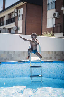Happy little boy on a ladder of the swimming pool - OCMF00527