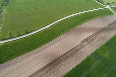 Aerial view of tractor in agricultural field, Franconia, Bavaria, Germany - RUEF02273