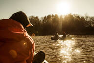 Caucasian fisherman sitting in canoe on river - BLEF12089