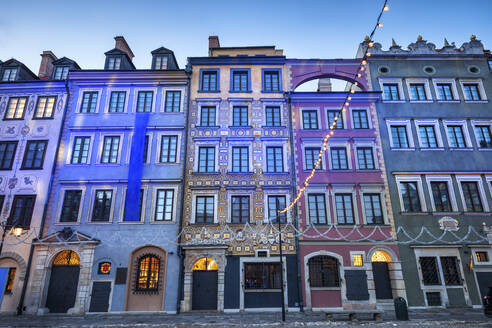 Poland, Warsaw, row of historic tenement houses at dusk in Old Town - ABOF00420