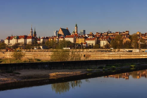 Poland, Warsaw, city skyline at sunrise, view across the Vistula River to the Old Town - ABOF00432