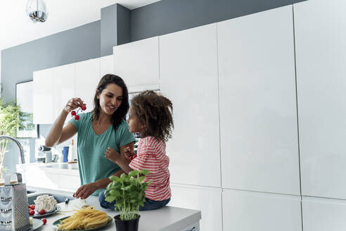 Mother and daughter cooking in kitchen together - ERRF01671