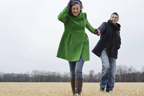 Caucasian couple walking in rural field - BLEF12177