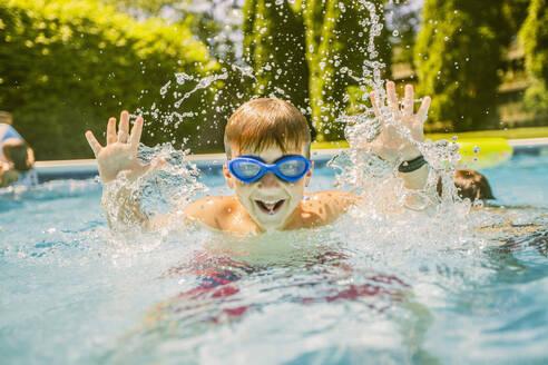 Boy splashing in swimming pool - BLEF12210