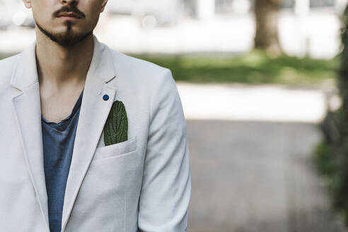 Man with green leave in his jacket pocket - KMKF01017