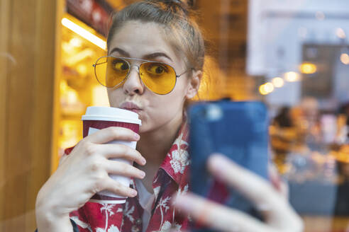 London, UK, girl in a cafe taking a selfie while drinking a coffee - WPEF01630