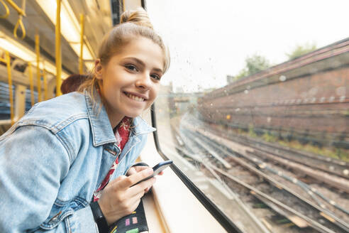 Portrait of smiling young woman travelling by train - WPEF01636